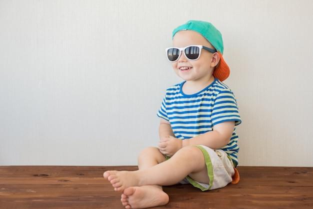 Menino sorridente, sentado no chão com óculos de sol