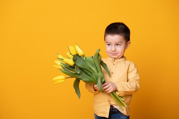 Menino sorridente sobre fundo amarelo do estúdio. criança feliz alegre com buquê de flores de tulipas.