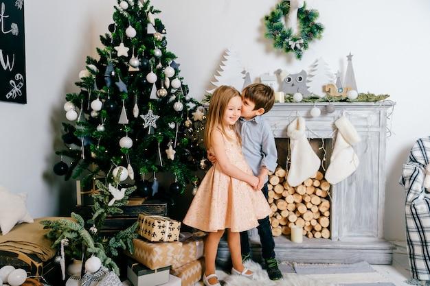 Menino sorridente, sussurrando no ouvido de sua namorada bonita e bonita no fron da árvore cristmas com lareira.