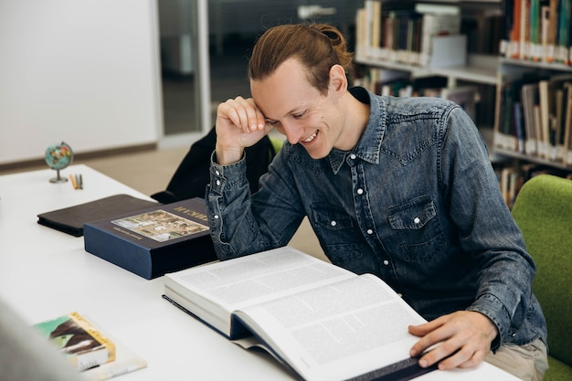 Menino sorridente trabalha com livro na mesa na biblioteca