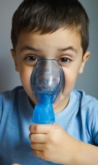 Menino sorridente usando o nebulizador e a máscara do inalador
