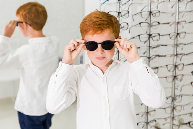 Menino sorridente, vestindo óculos pretos na clínica de óptica