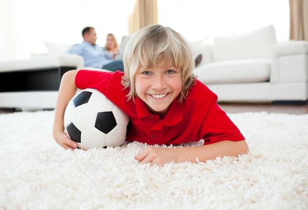 Menino sorrindo assistindo jogo de futebol deitado no chão