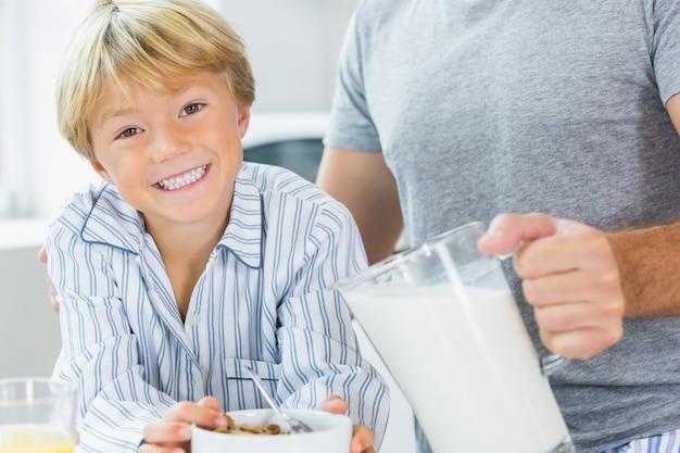 Menino sorrindo com cereal com pai derramando leite