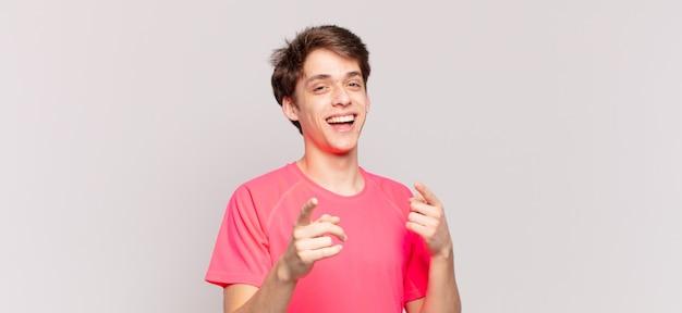 Menino sorrindo com uma atitude positiva, bem-sucedida e feliz apontando para a câmera, fazendo sinal de arma com as mãos
