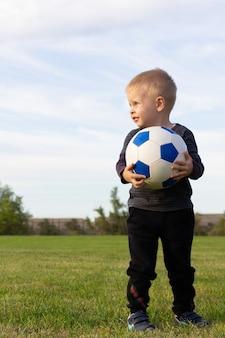 Menino sorrindo com uma bola de jogador de futebol
