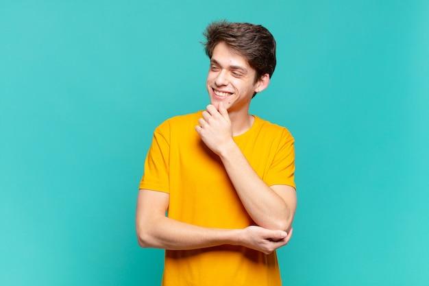 Menino sorrindo com uma expressão feliz e confiante com a mão no queixo, pensando e olhando para o lado
