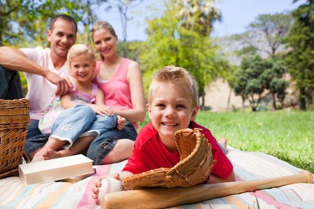 Menino sorrindo com uma luva de beisebol enquanto faz um piquenique com sua família