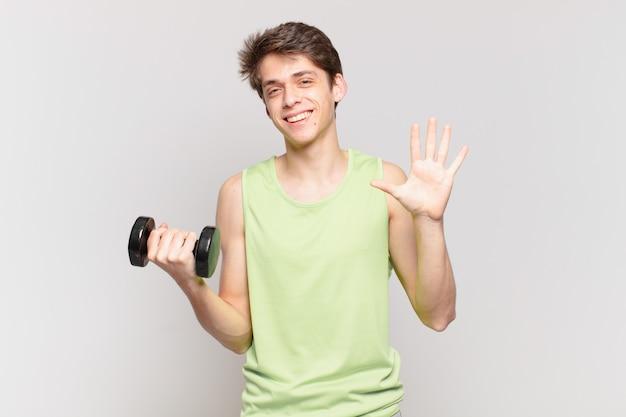 Menino sorrindo e parecendo amigável, mostrando o número cinco ou quinto com a mão para a frente, em contagem regressiva. conceito de haltere