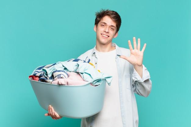 Menino sorrindo e parecendo amigável, mostrando o número cinco ou quinto com a mão para a frente, em contagem regressiva para o conceito de lavagem de roupas