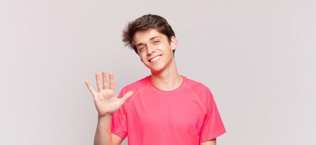 Menino sorrindo e parecendo amigável, mostrando o número cinco ou quinto com a mão para a frente, em contagem regressiva