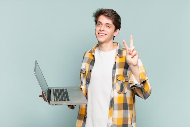 Menino sorrindo e parecendo amigável, mostrando o número dois ou o segundo com a mão para a frente, em contagem regressiva. conceito de laptop