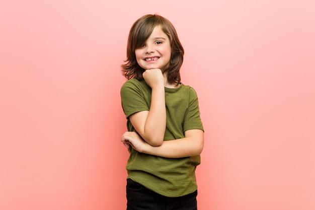 Menino sorrindo feliz e confiante, tocando o queixo com a mão.