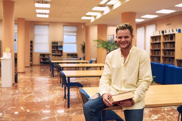 Menino sorrindo olha para a câmera com a biblioteca vazia