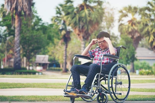 Menino sozinho ásia em cadeira de rodas, tendo uma dor de cabeça no parque