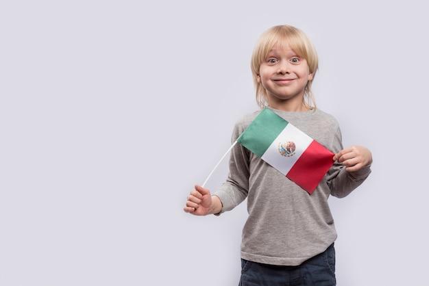 Menino surpreso com a bandeira do méxico nas mãos.