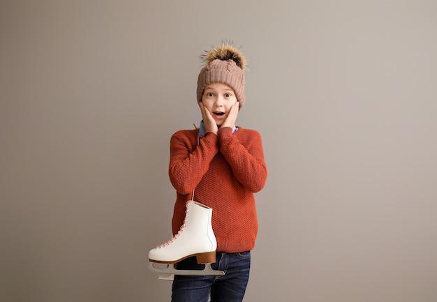 Menino surpreso com patins de gelo contra cinza