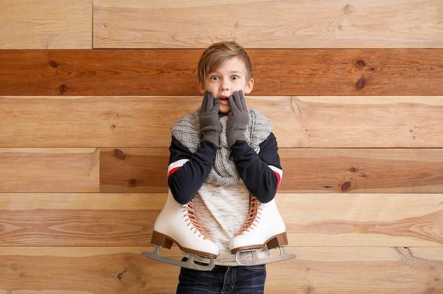 Menino surpreso com patins de gelo contra madeira