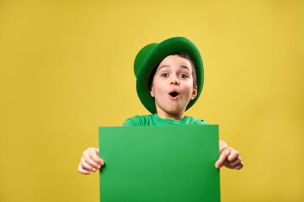 Menino surpreso com um chapéu de duende irlandês verde posando com uma folha de papel verde nas mãos