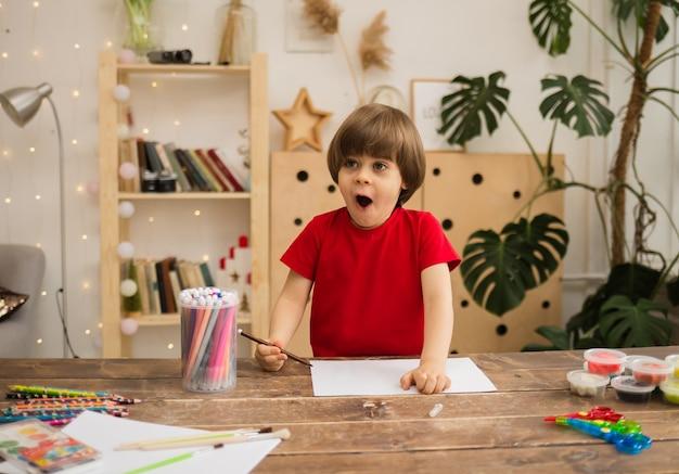 Menino surpreso desenhando com caneta de feltro colorida em papel branco em uma mesa de madeira com papel de carta na sala