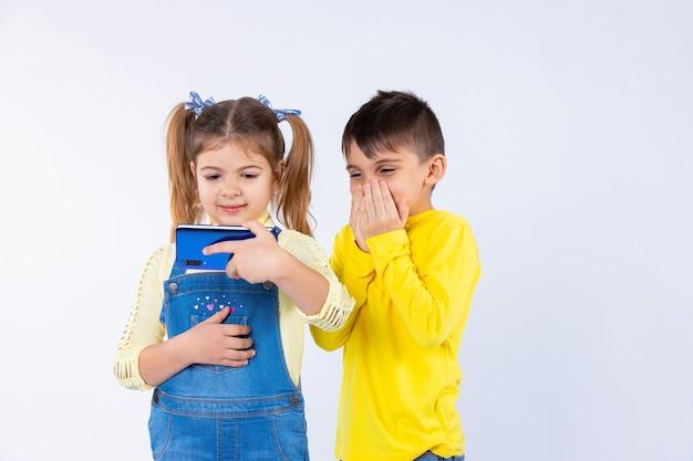 Menino surpreso em um fundo branco, sentado ao lado de uma garota com um smartphone.