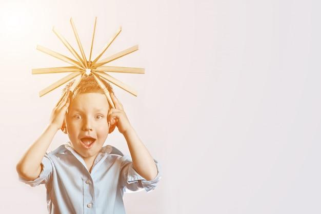 Menino surpreso em uma camisa azul e dirigir na cabeça na brilhante
