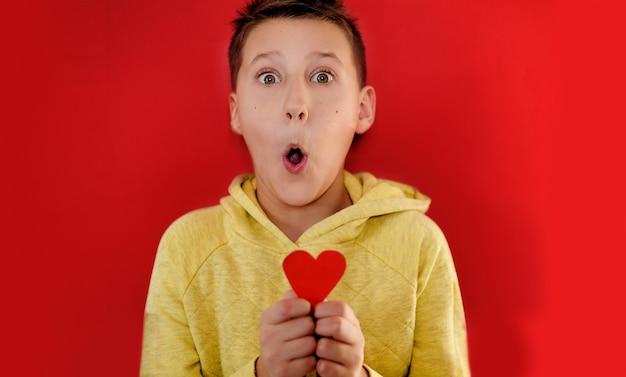 Menino surpreso em uma camiseta amarela mostra um coração de papel vermelho na parede vermelha.