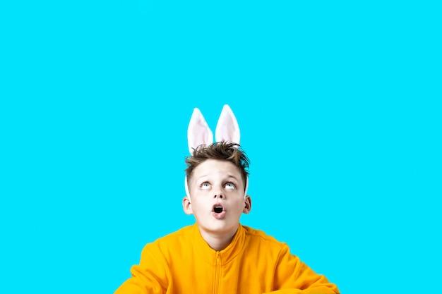 Menino surpreso em uma jaqueta amarela e orelhas de uma lebre em fundo azul