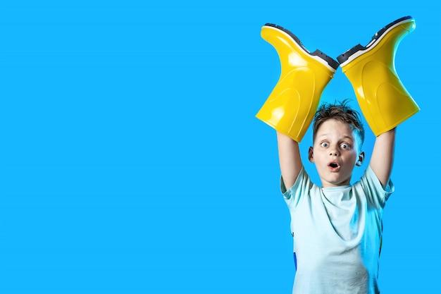 Menino surpreso enfiou as mãos em botas de borracha