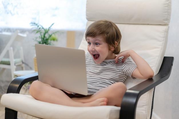 Menino surpreso usando laptop