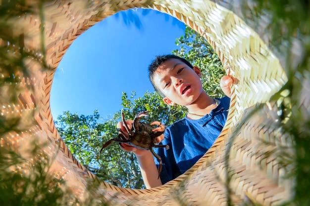 Menino tailandês fazendeiro pegar caranguejos nos seguranças felizes