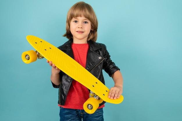 Menino tem skate amarelo nas mãos, sobre um fundo azul