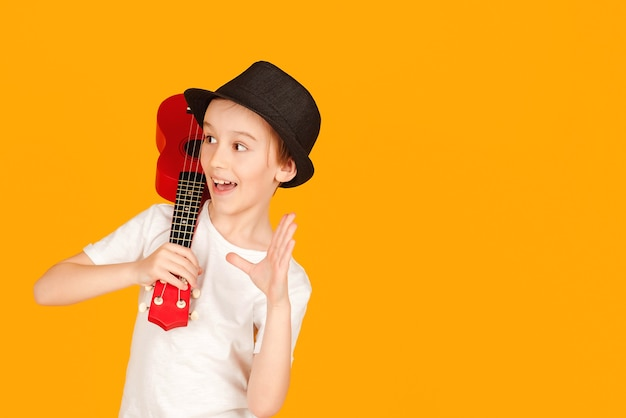 Menino toca guitarra havaiana ou cavaquinho. criança feliz curtindo a música. aluno aprendendo a tocar ukuleles. rapaz elegante com chapéu de verão isolado sobre fundo laranja.