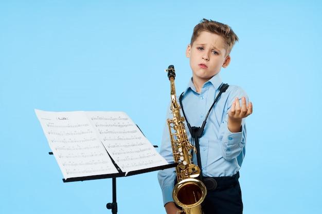 Menino toca saxofone