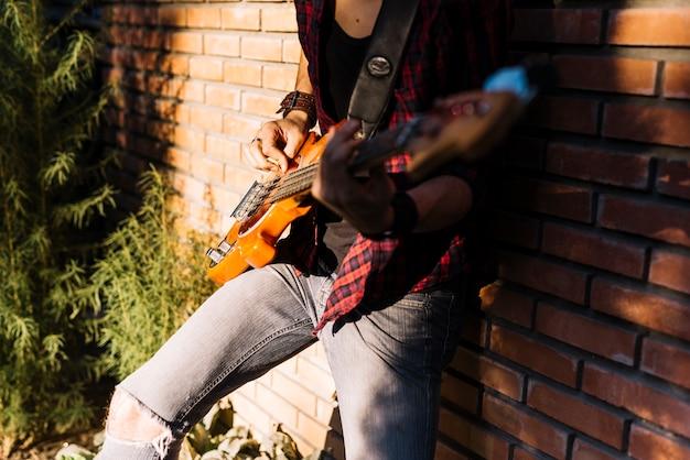 Menino, tocando, a, violão elétrico, ficar, ligado, parede tijolo