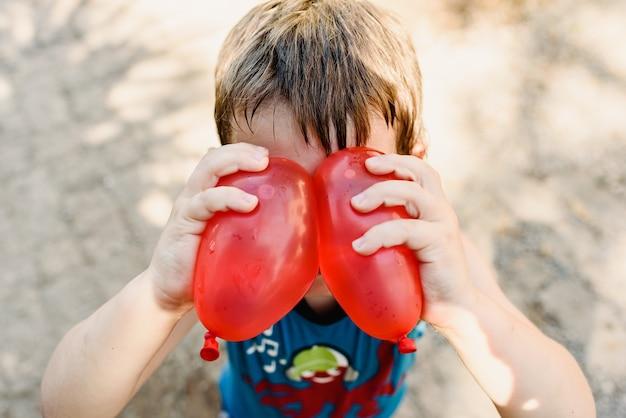 Menino, tocando, com, balões água, em, verão