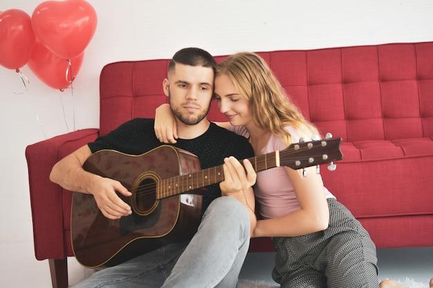 Menino tocando guitarra no quarto romântico felicidade no amor dia dos namorados