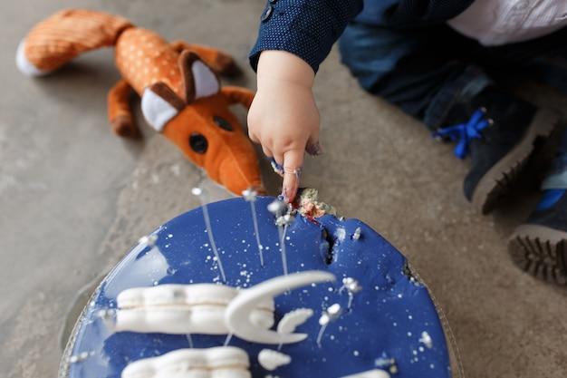 Menino tocando o bolo de aniversário com os dedos. conceito de festa do pequeno príncipe.