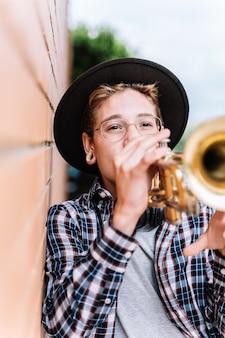 Menino tocando trompete na rua
