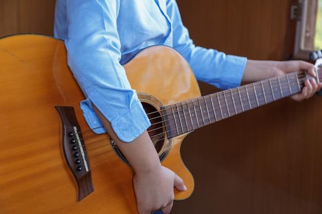 Menino tocando violão clássico se divertindo