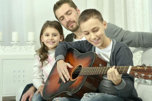 Menino tocando violão para sua família