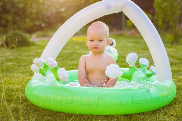 Menino toma banho ao ar livre. um garotinho está brincando no quintal