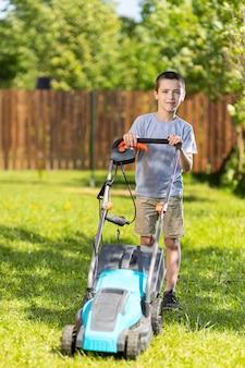 Menino trabalhador no jardim trabalhando no corte da grama com a ajuda de um moderno cortador de grama