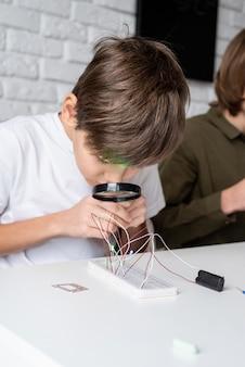 Menino trabalhando com luzes led em uma placa experimental para projeto de ciências usando lupa