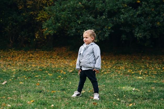 Menino travesso de 3-4 anos de idade correndo e brincando na floresta em um prado verde, feliz infância ativa