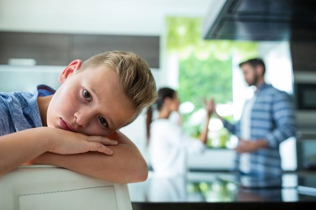 Menino triste, apoiando-se na cadeira enquanto os pais discutindo