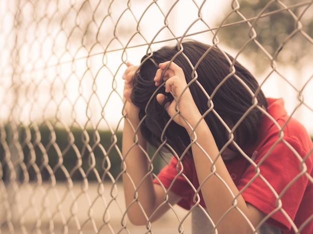 Menino triste atrás da rede da malha da cerca. conceito de emoções - tristeza, tristeza