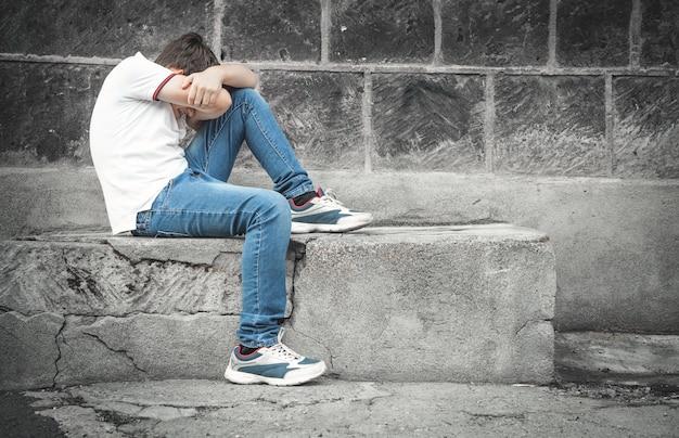 Menino triste caucasiano sentado na rua.