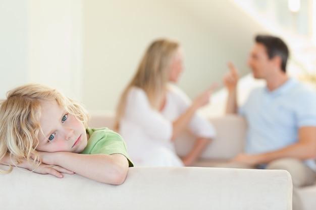 Menino triste com argumentos de pais atrás dele