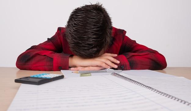 Menino triste com as mãos sobre a cabeça na mesa da escola